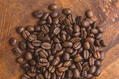 Brown roasted coffee beans, closeup macro on the wooden table for background and texture.  royalty free stock images