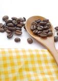 Brown roasted o feijão de café com a colher do chá no fundo branco Imagem de Stock
