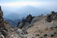 Brown rock on the background of the panorama of mountains of Tien Shan. Uzbekistan Stock Image