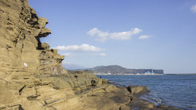 Brown rock cliff in the ocean on blue sky Stock Photography