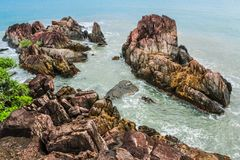 Brown Rock Formations Beside Ocean Stock Photo