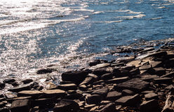 Brown rocky shore and water reflecting sunlight. Stock Image