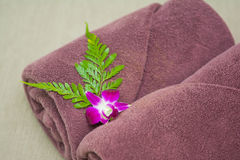 Brown roll with orchid on table in bedroom Royalty Free Stock Images