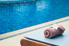 Brown roll towel with plumeria on beach chair Royalty Free Stock Photo