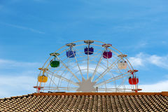 Brown roof, ferris wheel and blue sky Stock Photos