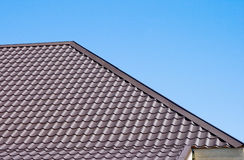 Brown roof of metal roofing on the sky background Stock Photo