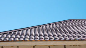 Brown roof of metal roofing on the sky background Royalty Free Stock Photo