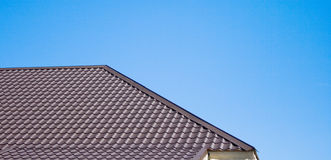 Brown roof of metal roofing on the sky background. Brown roof of metal roofing on the sky Stock Image