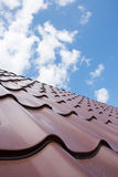 Brown roof of metal roofing on the sky. Background Stock Images