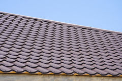 Brown roof of metal roofing on the sky background. Brown roof of metal roofing on the sky stock images