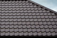 Brown roof tiles or shingles on house as background image. New overlapping brown classic style roofing material texture pattern o. N a actual house stock photography
