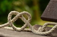 Brown Rope Tangled and Formed Into Heart Shape on Brown Wooden Rail Stock Photos