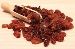 Brown-Rosinen mit Löffel auf Holztisch, gesunde Ernährung Stockfoto