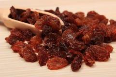 Brown-Rosinen mit Löffel auf Holztisch, gesunde Ernährung Lizenzfreies Stockfoto