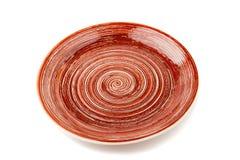 Brown round ceramiczny talerz z spirala wzorem na bielu, odosobnionym fotografia stock