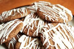 Brown Round Christmas Gingerbread cookies drizzled with White Chocolate on a plate.  Royalty Free Stock Photos