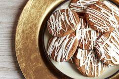 Brown Round Christmas Gingerbread cookies drizzled with White icing on a golden plate.  Royalty Free Stock Photography