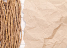 Brown rumpled cardboard paper background with marine rope Royalty Free Stock Image