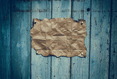 Brown rumpled kraft paper hanging on a blue wooden surface Stock Photography