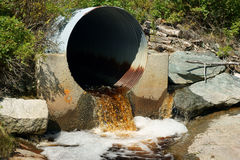 Brown runoff water from rusted culvert Royalty Free Stock Image