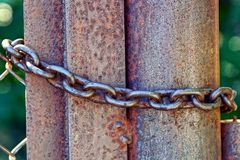 Brown rusty iron pipe and steel chain on the fence. Fence fragment with rusty column and steel chain Stock Image