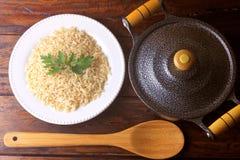 Brown ryż gotujący w naczyniu obok garnka i bambusa łyżki w kuchni na nieociosanym drewnianym stole obrazy royalty free