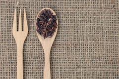 Brown ryż w drewnianej łyżce na workowym textu (Ryżowa jagoda) zdjęcia royalty free