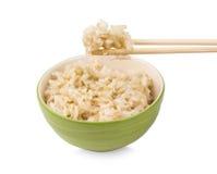 Brown ryż z chopsticks w filiżance na białym tle Fotografia Royalty Free