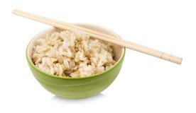 Brown ryż z chopsticks w filiżance na białym tle Zdjęcie Royalty Free