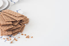 Brown rye crispy bread Swedish crackers on piece of cloth with plates on white background with space for text Royalty Free Stock Photos