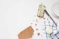 Brown rye crispy bread Swedish crackers with spread cottage cheese, decorated with thin green onion, on piece of cloth Stock Photo