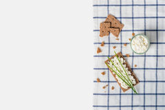 Brown rye crispy bread Swedish crackers with spread cottage cheese, decorated with thin green onion, on piece of cloth on white Stock Photo