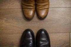 Brown rzemienni buty na drewnianej podłoga Obrazy Royalty Free