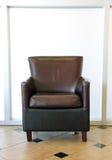 Brown rzemienny krzesło na dachówkowej podłoga Obrazy Stock