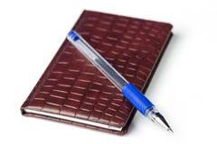 Brown rzemienny notatnik z błękitnym piórem odizolowywającym na bielu z selekcyjną ostrością Obrazy Stock
