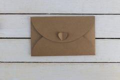 Brown rzemiosła koperta na białym drewnianym tle zdjęcia stock