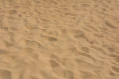 Brown sand at the beach There are traces of people walking. Stock Photo
