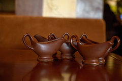Brown sauce boats on table. Close up empty brown gravy boats standing on table royalty free stock images
