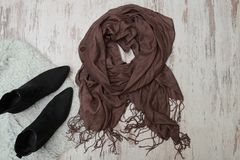 Brown scarf and black shoes on wooden background. Fashionable co. Ncept royalty free stock image