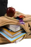 Brown School Back Pack full of school supplies and an apple. Brown school back pack full of school supplies with paper, folders and pencils, courdoroy, and an stock image