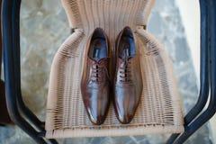Brown-Schuhe auf einem Stuhl Stockfotografie