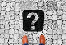 Brown-Schuhe, die auf dem Boden mit Fragezeichen - Bedeutung des lebens- folgenden Reiseziels stehen stockbild