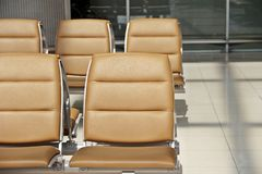 Indoor waiting seat. Brown seats in airport waiting area for departure flight Royalty Free Stock Image
