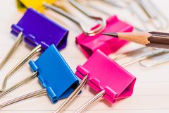Brown sharpened pencil point with an assortment of colorful pape. R clips with blurred background Royalty Free Stock Image