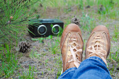 Brown shoe of hipster girl in jeans relaxation on the grass and listening music in green summer park. Stock Image