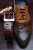 Brown shoes and belt on wooden table. Classic brown shoes and belt on wooden table Royalty Free Stock Photography