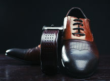 Brown shoes and belt on wooden table. Classic brown shoes and belt on wooden table Royalty Free Stock Photo