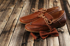 Brown shoes with bow tie. Fashion brown shoes with bow tie on a brown wooden table Stock Image