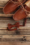 Brown shoes with bow tie. Fashion brown shoes with bow tie on a brown wooden table Royalty Free Stock Photos