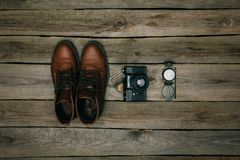 Brown shoes with film camera and compass. Flat lay of brown shoes with film camera and compass on a wooden table Stock Photo